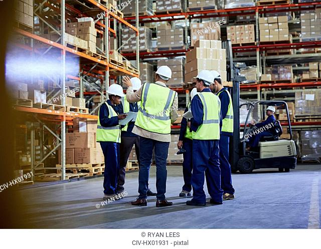 Manager and workers meeting in distribution warehouse