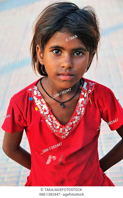 Young girl at the other side of the Har Ki Pairi main ghat by the Ganges river where pilgrims cook and sleep