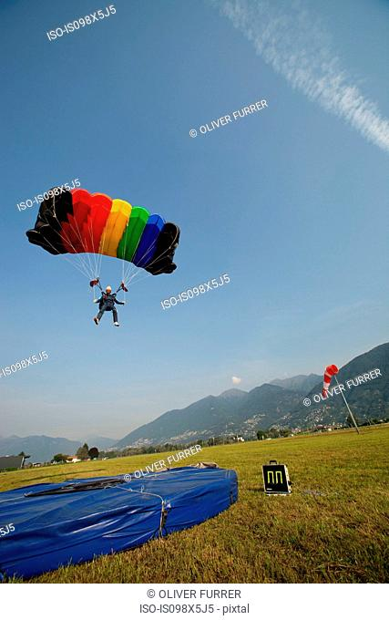 Skydiver with parachute over Locarno, Tessin, Switzerland