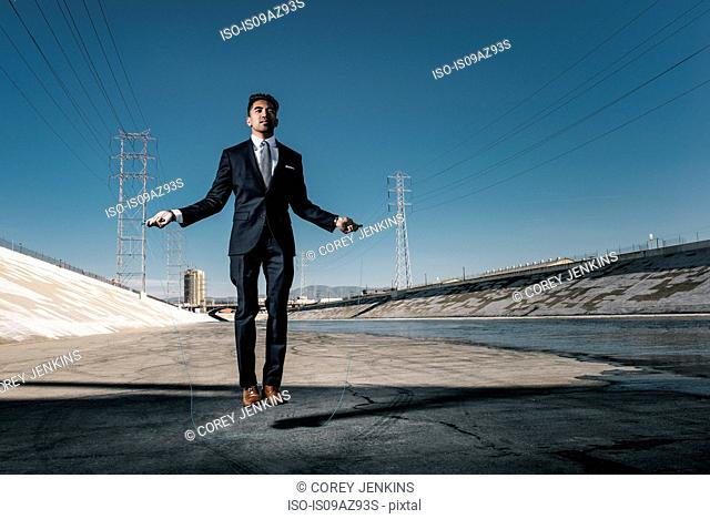 Businessman skipping, Los Angeles river, California, USA
