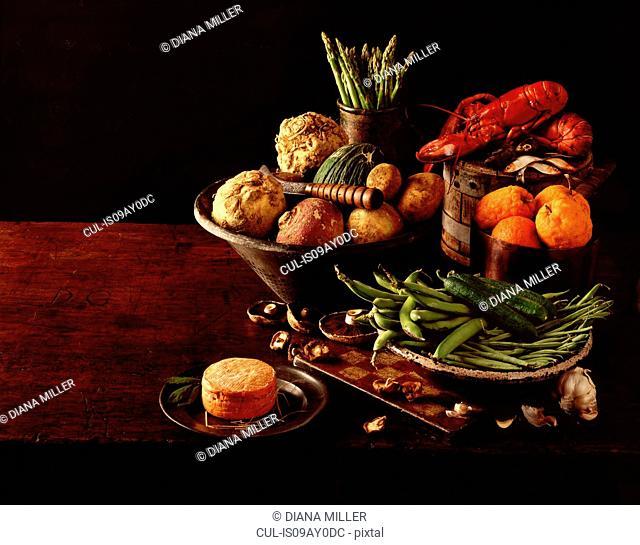 Still life of fresh lobster, fruit and vegetables