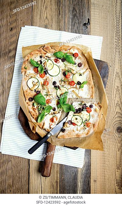 Mediterranean tarte flambée with cream cheese, courgettes and olives