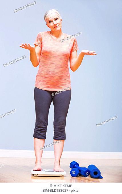 Caucasian woman shrugging on yoga mat
