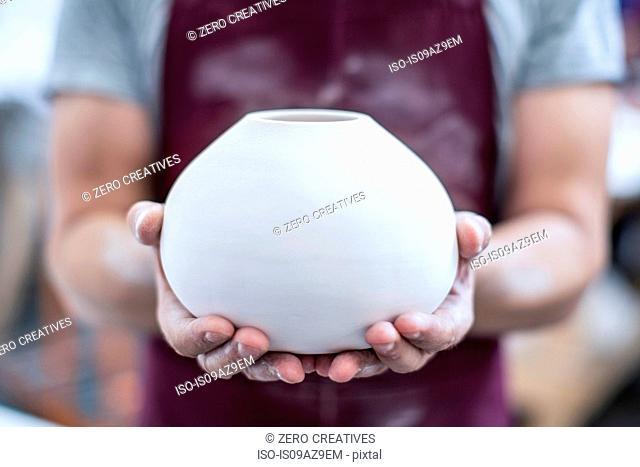 Hands of male potter holding finished vase in workshop