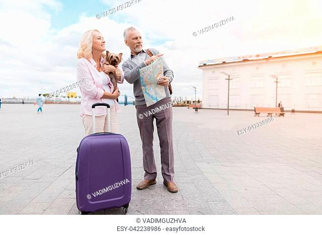 An elderly couple walks along the embankment with their little dog. They go and carry a purple travel bag. They are happy to get out on an interesting trip