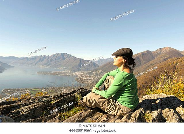 Woman with Flat Cap Sitting and Enjoy Panoramic View Over Mountain and Alpine Lake Maggiore in Ticino, Switzerland
