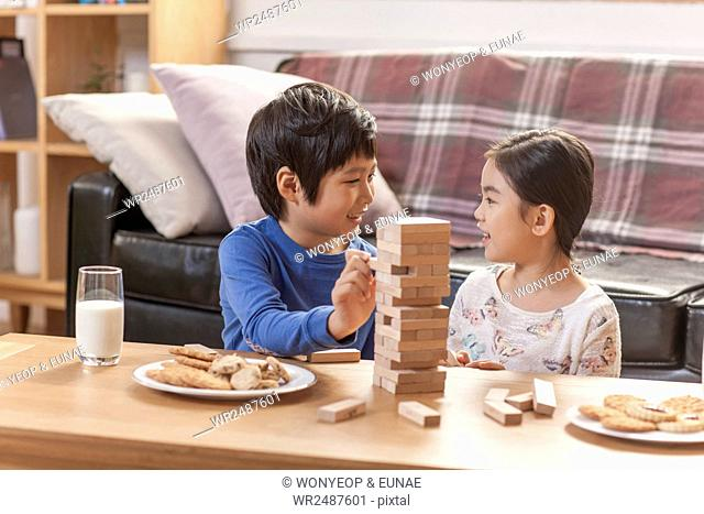 Side view portrait of smiling boy and girl face to face with a board game and cookies on a table