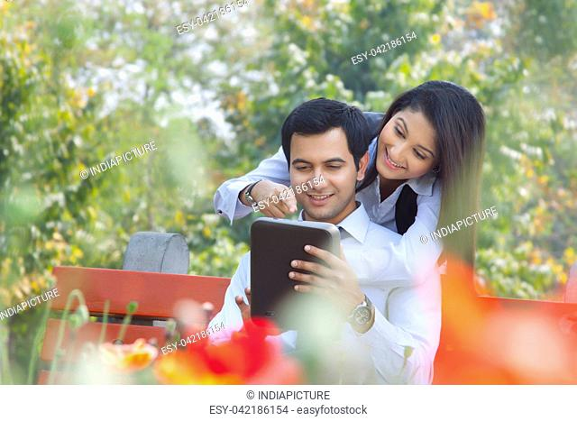 Businessman and businesswoman working in a park