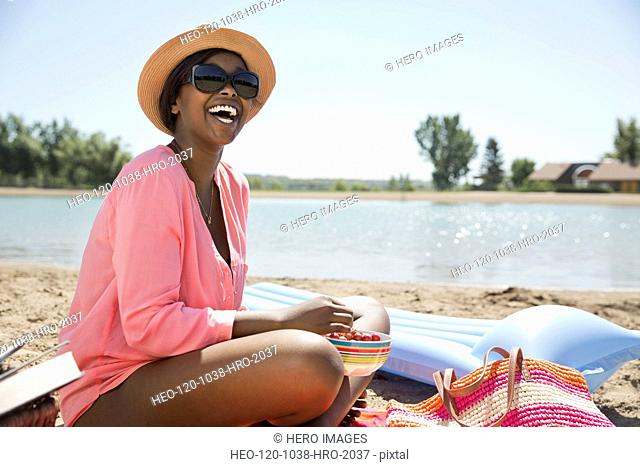 Cheerful woman sitting on beach