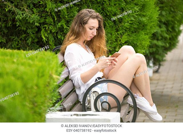Young girl writes a message on the phone, on a park bench