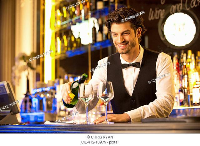 Well dressed bartender pouring wine