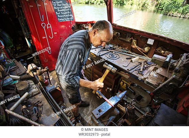 High angle view of blacksmith at his workbench on his working boat on the water, hammering hot metal