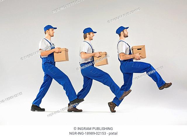Three builders walking with boxes