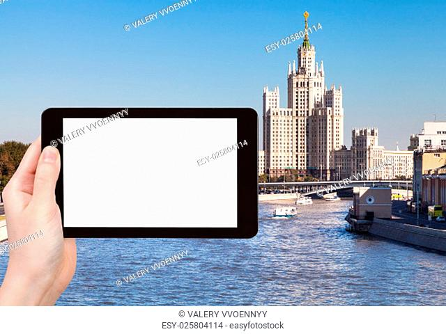 travel concept - hand holds tablet pc with cut out screen and Moscow vysotka - skyscraper on background