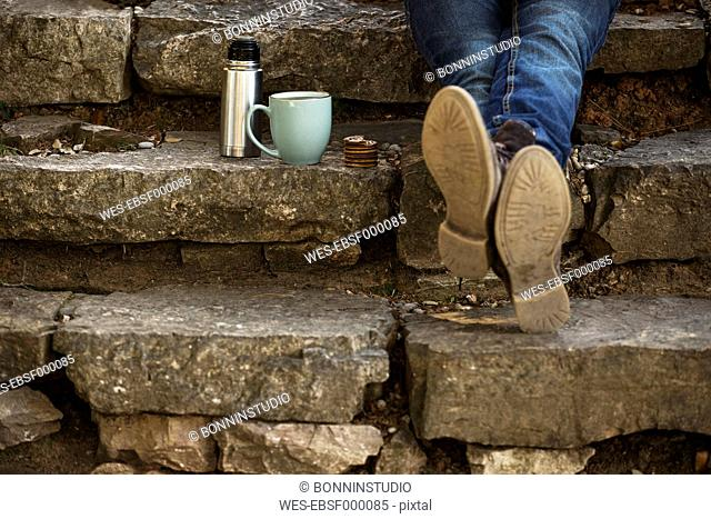 Feet of young man sitting on steps with cup of coffee and thermos flask having a break