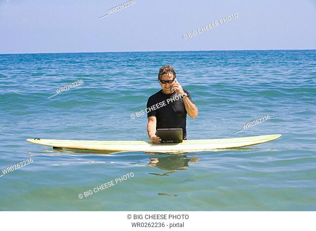 Man talking on a phone and using a laptop in the sea