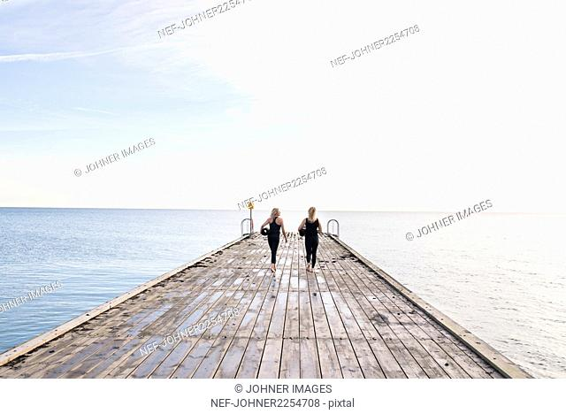 Two women carrying exercise mats, walking on pier