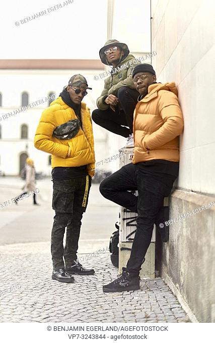 three stylish male friends together at street, wearing urban fashion trend outfit, in city Munich, Germany