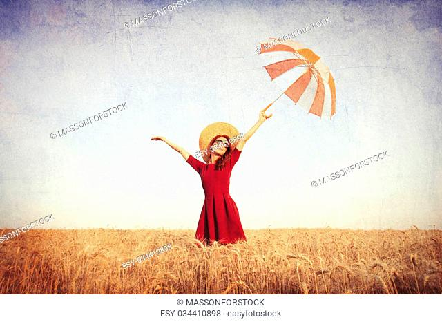 Girl in red dress with umbrella and hat on wheat field in summer time