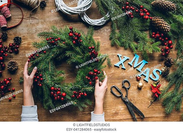 top view of female hands holding Christmas wreath with fir branches and decorative berries, with word Xmas on wooden tabletop