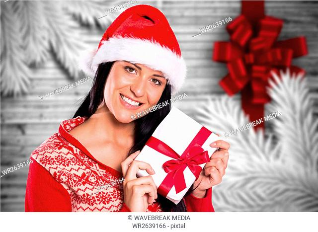 Beautiful woman in santa hat holding a christmas gift