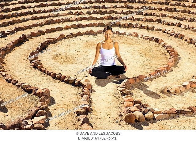 Mixed race woman meditating in zen garden