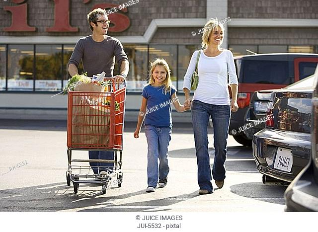 Family leaving supermarket, man pushing shopping trolley in car park, mother holding daughter's hand, smiling, front view