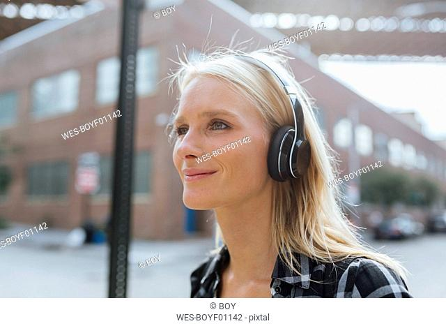 USA, New York City, Brooklyn, smiling young woman listening to music with headphones in the city