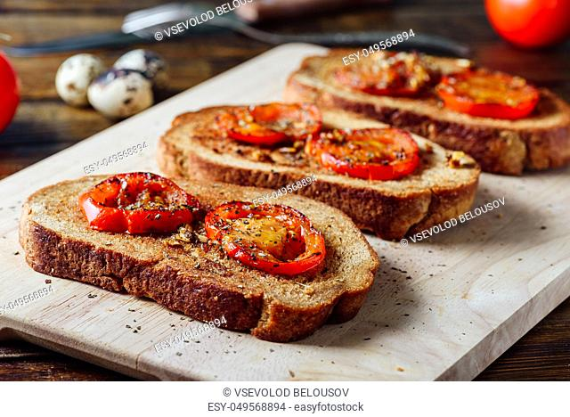 Three Bruschettas with Fried Tomatoes on Cutting Board