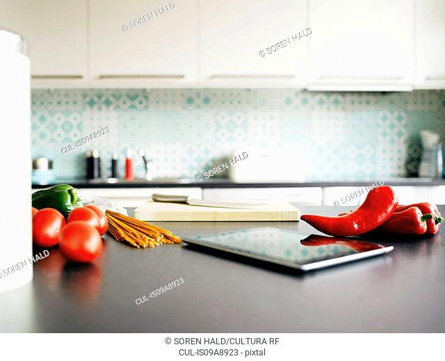 Digital tablet, red peppers and tomatoes on kitchen counter