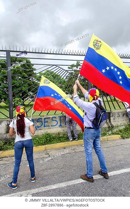 Demonstrator waving the Venezuelan flag in front of the military base. Opposition protesters assembled on the Francisco Fajardo motorway