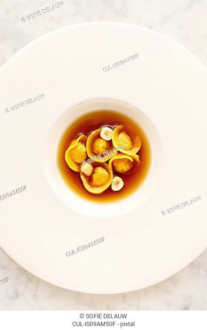 Ravioli, hazelnuts in broth