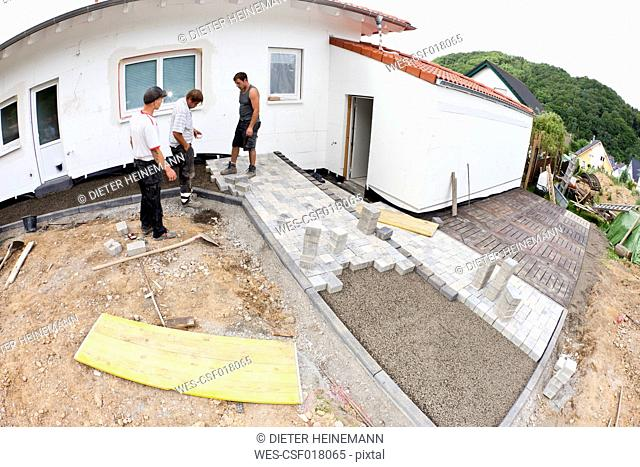 Germany, Rhineland Palatinate, Workers assembling paving stone