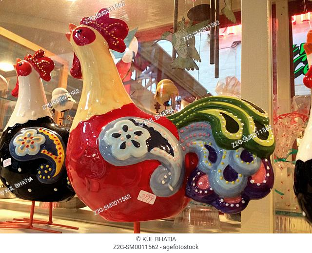 Colourful porcelain roosters on display greet and await customers in a curio shop, Ontario, Canada