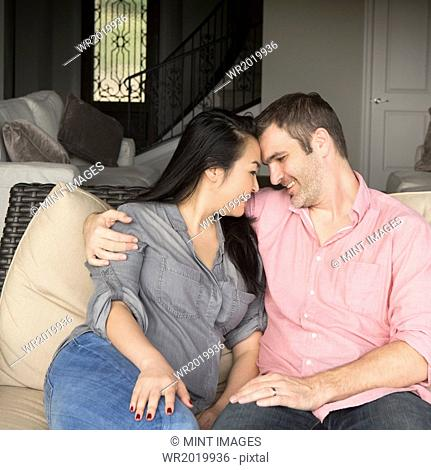Smiling man and woman sitting on a sofa, hugging, and looking at each other