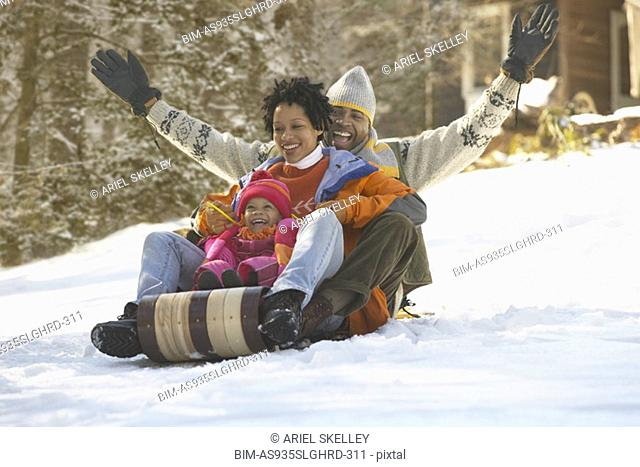 African family riding on sled and laughing