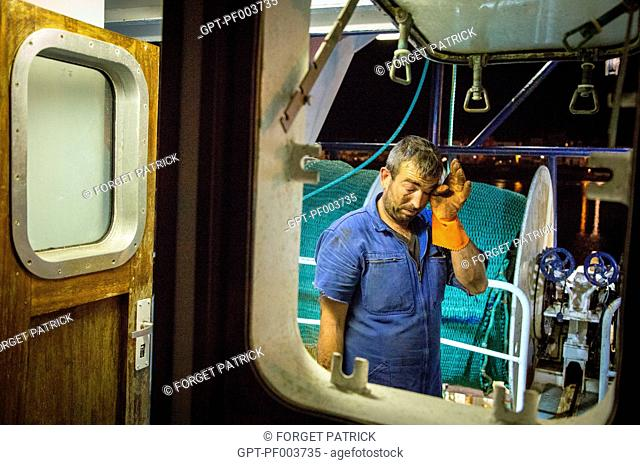 EXHAUSTION ON THE BRIDGE AT NIGHT WITH THE RAISING OF THE HAUL, SEA FISHING ON THE SHRIMP TRAWLER 'QUENTIN-GREGOIRE' OFF THE COAST OF SABLES-D'OLONNE (85)