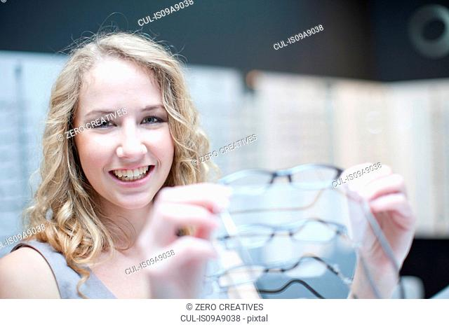 Young woman looking at eyeglasses