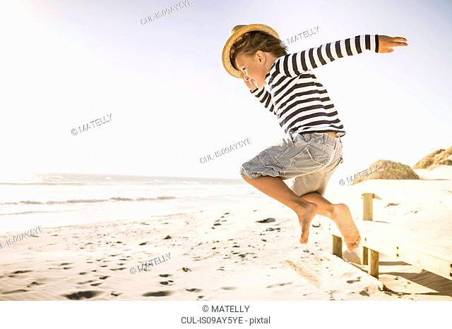 Young boy jumping on beach, wearing straw hat
