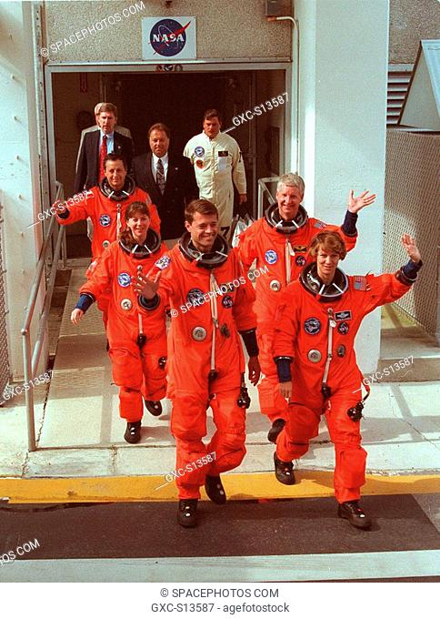 06/24/1999 --- After suiting up for their practice countdown exercise, STS-93 crew members wave to onlookers as they head for the bus outside the Operations and...