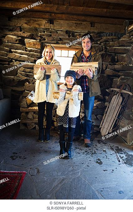 Portrait of family in rustic house holding logs