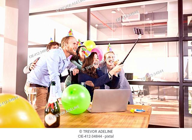 Playful business people celebrating birthday taking selfie with selfie stick in conference room