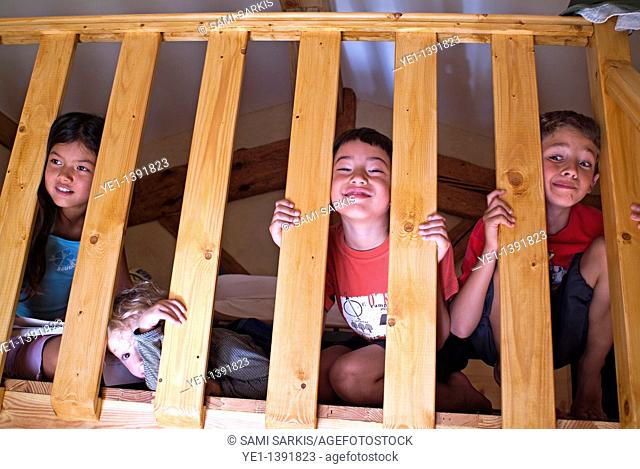 Four children playing on a mezzanine balcony and making faces through the handrail, France