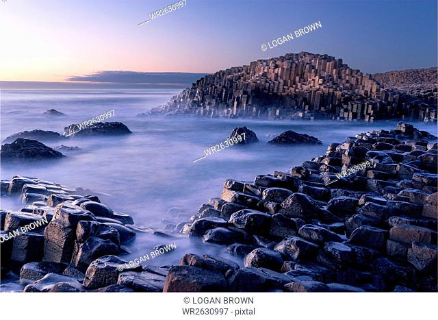 The Giant's Causeway rises out of the Atlantic late at night as the last light of the sun disappears below the horizon, County Antrim, Northern Ireland