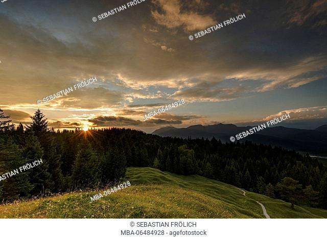View from the Kranzberg at Mittenwald, as the setting sun with sunrays and nice beautyful clouds. A small path writhes in the direction of edge of the forest...