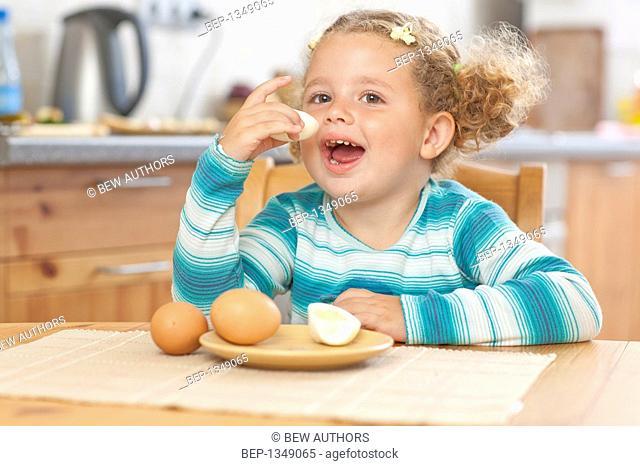 Adorable girl eating boiled eggs