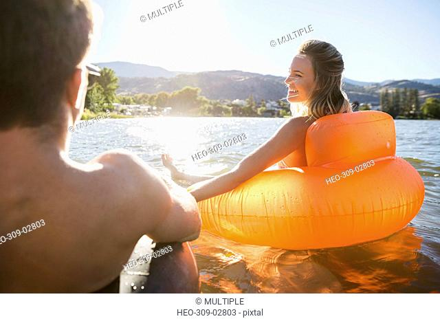 Young couple holding hands in inflatable rafts on sunny summer lake