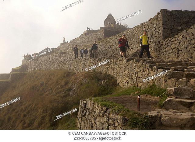 Tourists at the Industrial Sector in front of the Hut of the Caretaker of the Funerary Rock, Machu Picchu, Cusco Region, Peru, South America