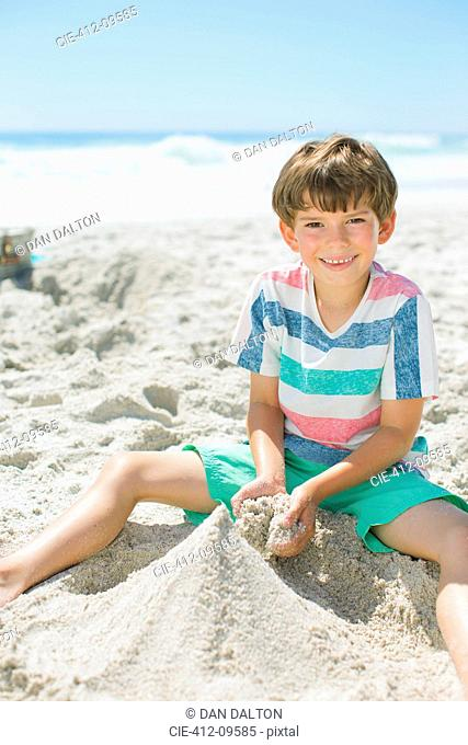 Boy building sandcastle on beach