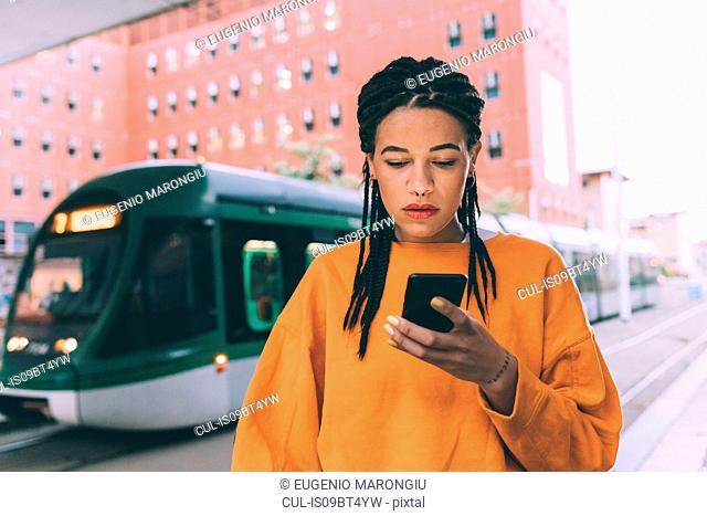 Woman texting at tram stop, Milan, Italy